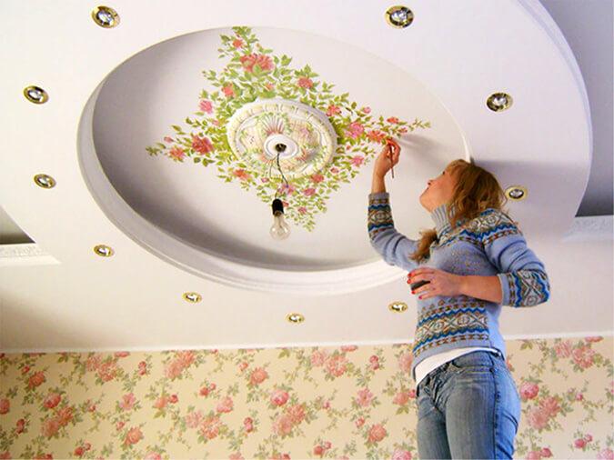 Женщина расписывает натяжной потолок