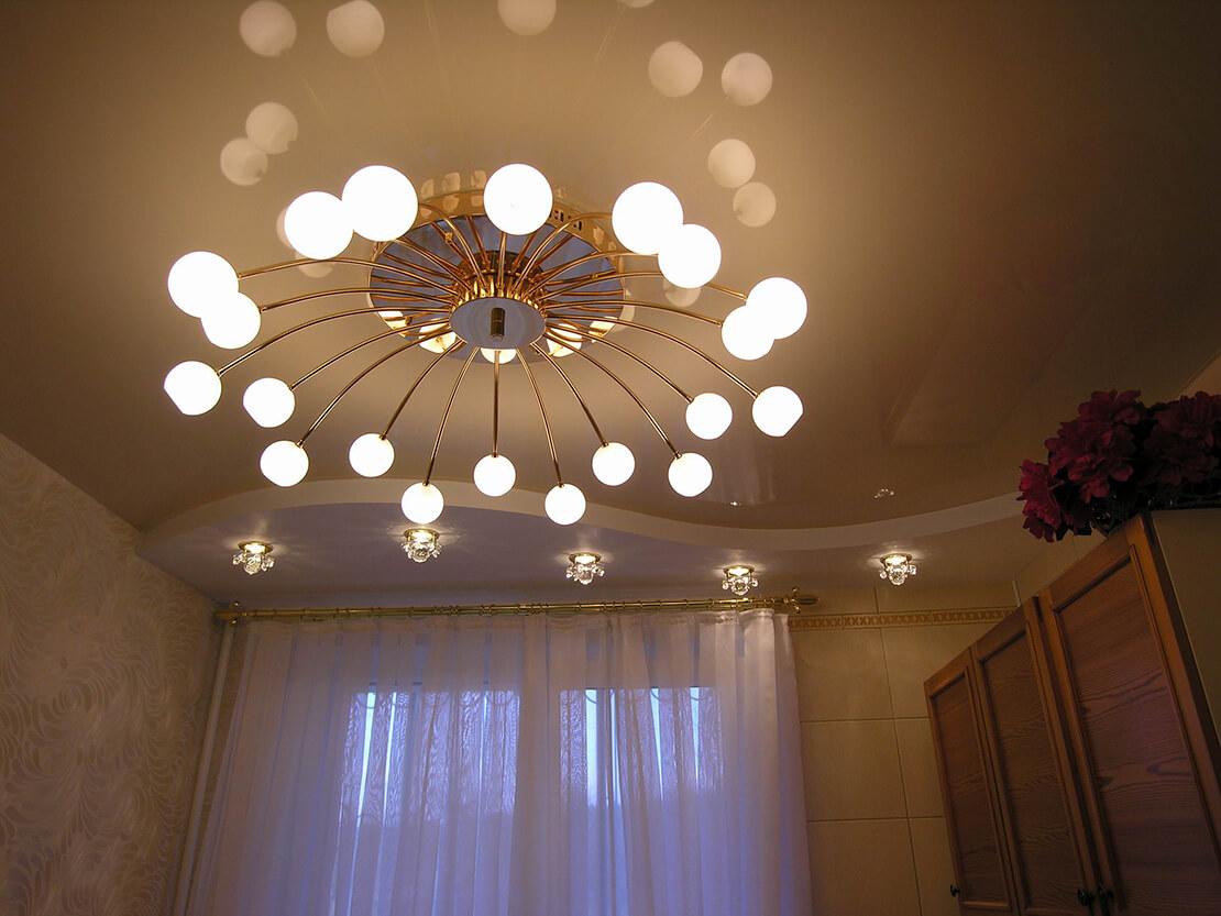 Глянцевый натяжной потолок в гостинной и люстра