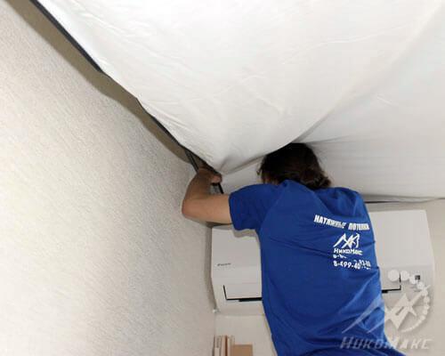 Монтажник делает натяжку натяжного потолка