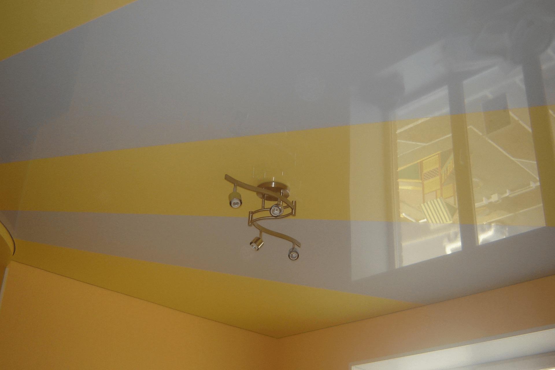 Спайка полотен в виде солнца на потолке в квартире