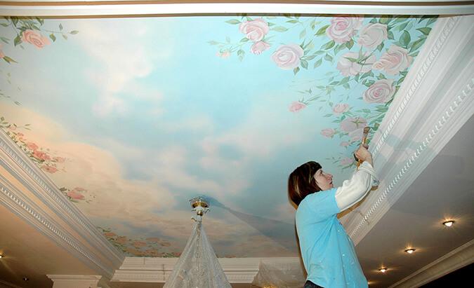 женщина разрисовывает натяжной потолок